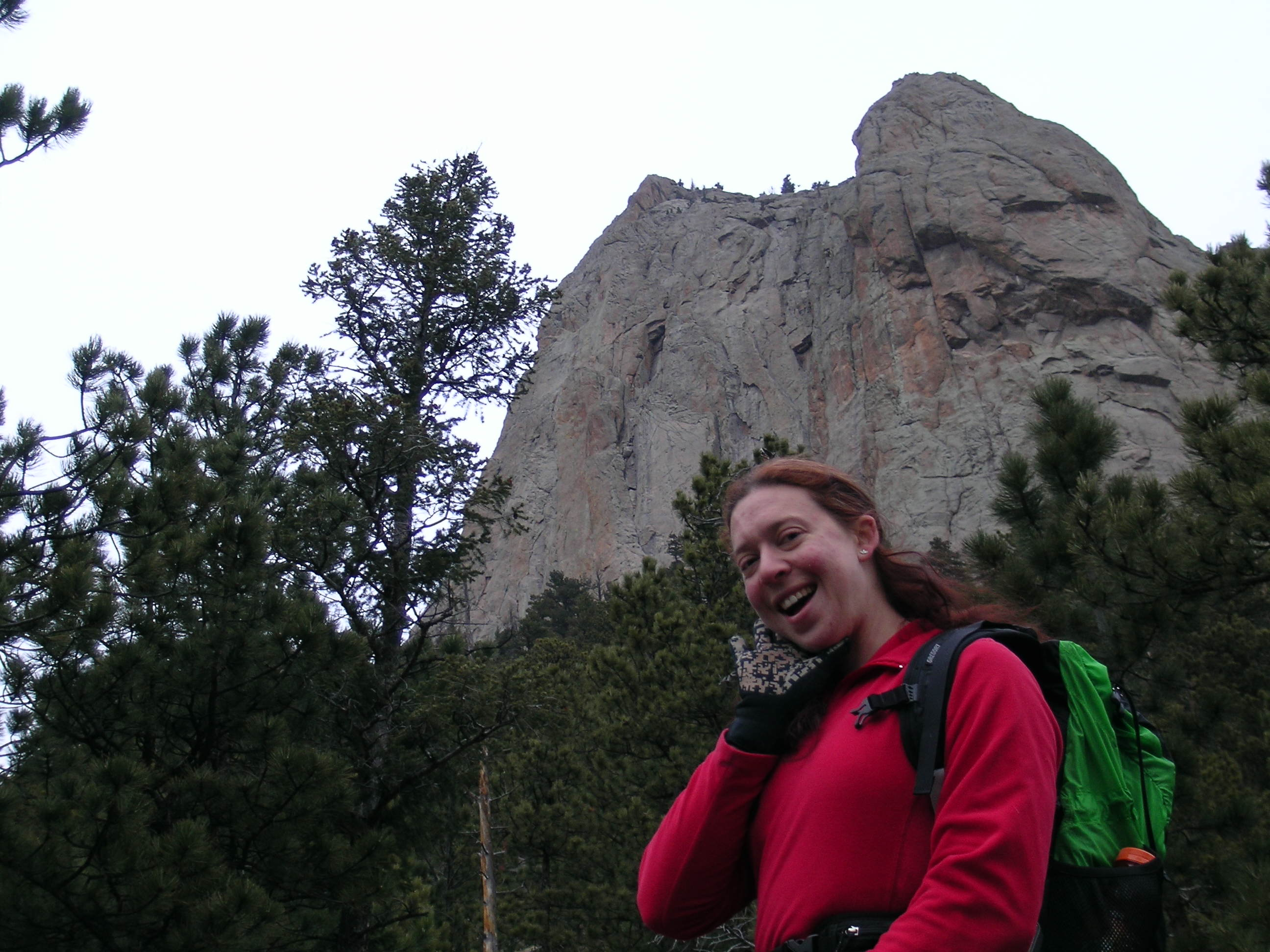 Clare smiles in front of Sundance Buttress, Estes Park
